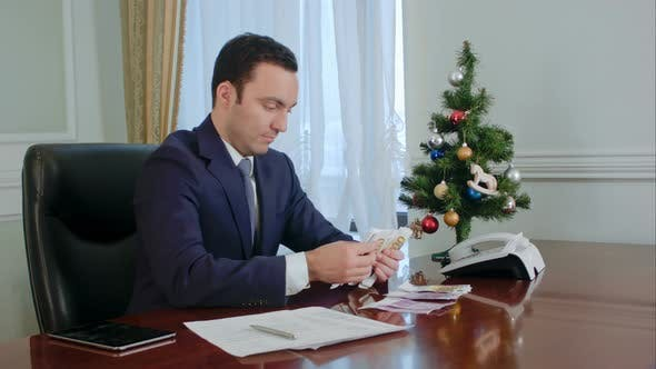 Thumbnail for Happy Young Businessman Counts Salary Near New Year Tree in Office