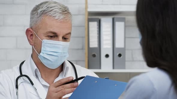 Doctor Wearing Face Mask Talking With Patient In Clinic Indoors