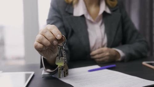 Estate Agent Midsection Offering Keys To Camera