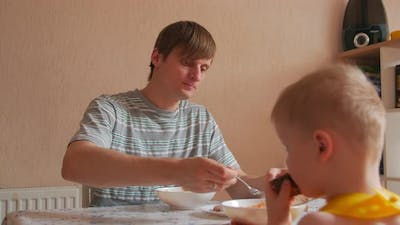 Man Eating Dinner With Boy