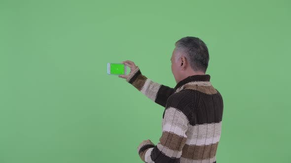Thumbnail for Rear View of Mature Japanese Man Taking Picture with Phone