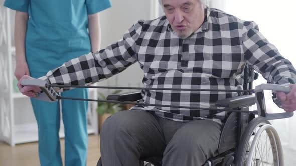 Thumbnail for Elderly Grey-haired Caucasian Man in Wheelchair Exercising As Professional Unrecognizable Nurse