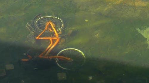 Fahrrad auf dem Boden des schmutzigen Teiches