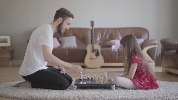 Thumbnail for Young Bearded Father and Little Girl with Long Hair Playing Chess Sitting on the Floor on Fluffy