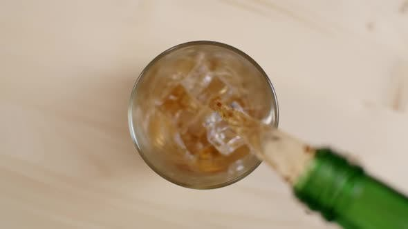 Thumbnail for Top View Cold Rum or Whiskey Drink Pouring From Green Bottle in Glass With Ice Cubes Wooden Table
