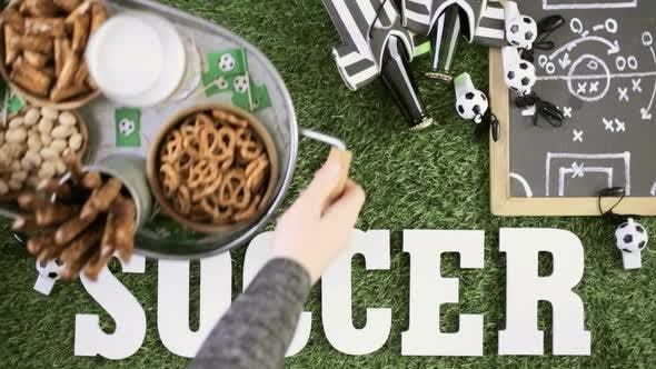 salty snacks and drinks on the metal tray for soccer party.