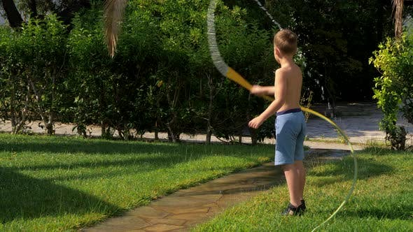 Child Having Fun When Watering Lawn with Hose