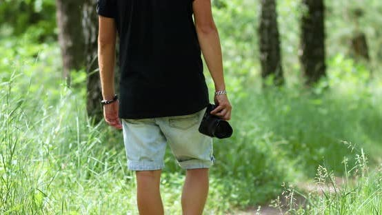 Man Photographer with a Photo Camera in Hand Walk Outdoor
