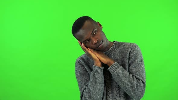Thumbnail for A Young Black Man Sleeps with the Head on His Hands, He Wakes Up and Stretches - Green Screen Studio