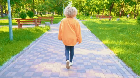 Thumbnail for Back View Woman with Curly Blond Hair Stroll in Park