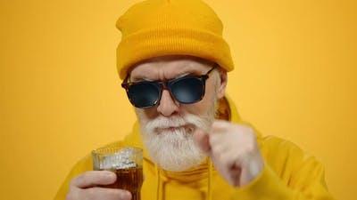 Cheerful Elderly Man Drinking Juice in Studio