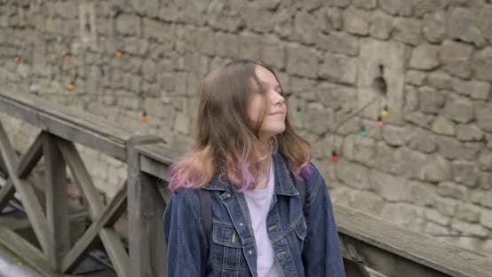 Thumbnail for Smiling Teenager Girl with Purple Hair in Denim Jacket Walking in the Old Tourist Town