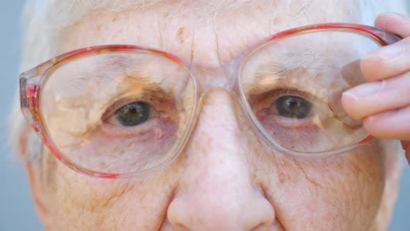 Detail Portrait of Granny in Eyeglasses with Pensive Sight. Close Up Wrinkled Face of Female