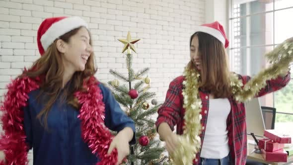 Happy Asian women celebrate christmas party with friends in office.