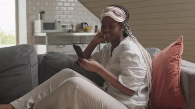 African American Woman Scrolling on Smartphone at Home