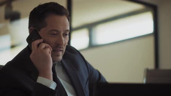 Thumbnail for Close up of a businessman talking on the phone while working from his office. Slow motion