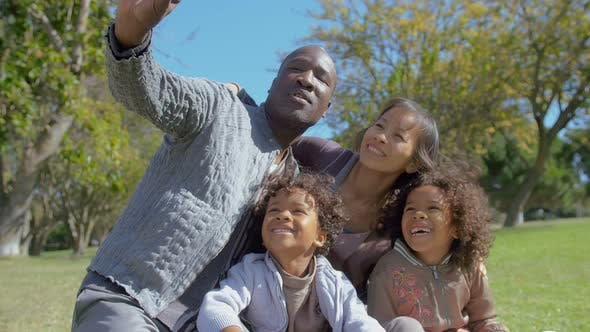 Thumbnail for Happy Multiethnic Family Taking Selfie on Smartphone in Summer Park in Slow Motion