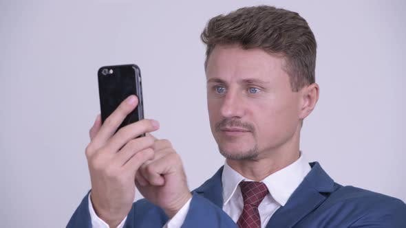 Cover Image for Face of Happy Bearded Businessman Smiling While Using Phone