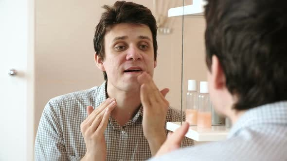 Thumbnail for Man Puts Cream on His Face After Shaving While Looking in the Mirror