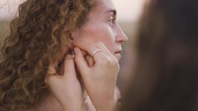 Young Woman Put on Earrings to Her Girlfriend Outdoors