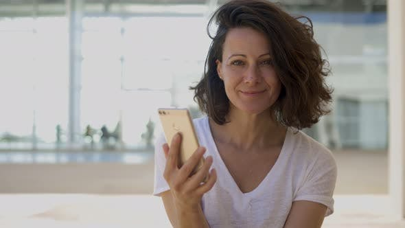 Thumbnail for Smiling Brunette Woman Holding Smartphone and Looking at Camera