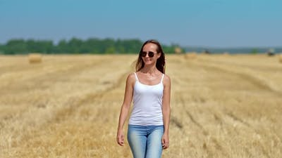 Happy Woman in Sunglasses Walks Through the Countryside