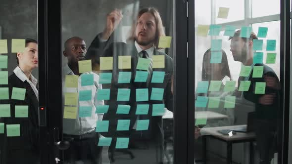 Business Meeting International Management Team at Work Team Is Standing Next To a Glass Board with