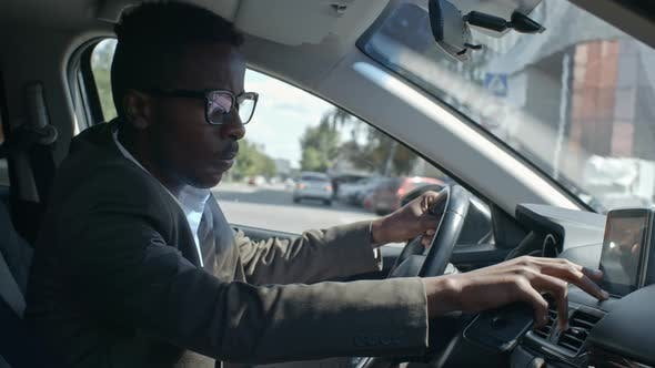 Thumbnail for African Businessman Sitting into Car and Setting Up GPS Navigator