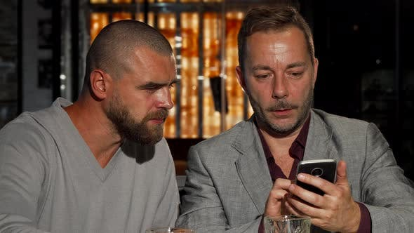 Cover Image for Mature Man Showing His Friend Something on Smart Phone While Dronking Whiskey