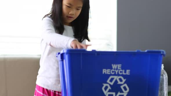 Thumbnail for Young girl putting bottles in recycle bin
