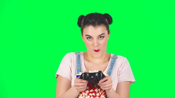 Thumbnail for Girl Playing a Video Game and Chews Popcorn on a Green Screen, Slow Motion
