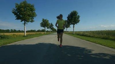 Happy Woman Running on Empty Street