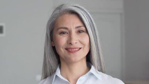 Headshot of Senior 50 Years Old Asian Businesswoman on Grey Background