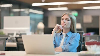 Young Woman Sitting in Office and Thinking
