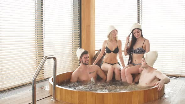 Thumbnail for Two Loving Couple Enjoying Hot Wooden Whirlpool with Warm Water in Modern Bathhouse