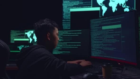 Asian Boy Hacker Hacking With Multiple Computer Screens In Dark Room