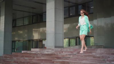 Beautiful confident business woman in glasses and descends stairs.