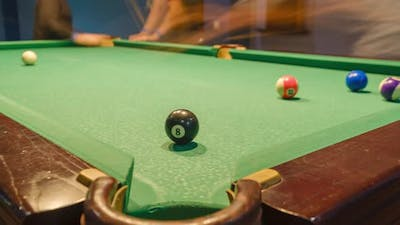 Billiard balls with numbers on a pool table. time lapse shot with slider