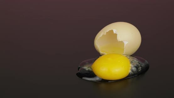 Thumbnail for Egg Yolk Poured Out From Broken Eggshell on Black Surface