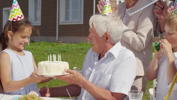 Thumbnail for Girl Bringing Birthday Cake to Grandfather on Outdoor Family Dinner
