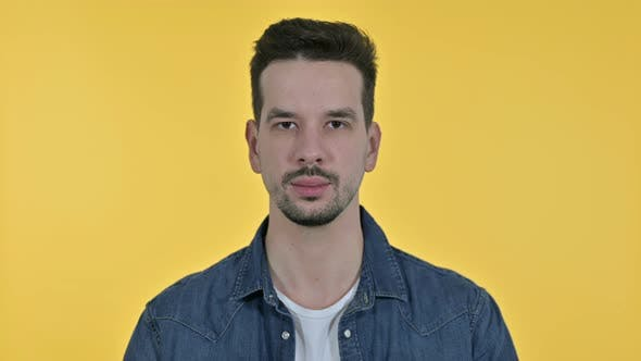 Thumbnail for Portrait of Young Man Looking at the Camera, Yellow Background