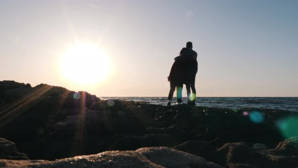 Couple standing on edge of shore at sunset