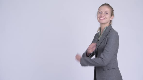 Thumbnail for Profile View of Young Happy Blonde Businesswoman Looking at Camera with Arms Crossed
