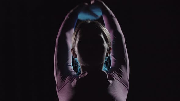 Young Female Gymnast on Training  Warming Up  Neon Contrast Lighting