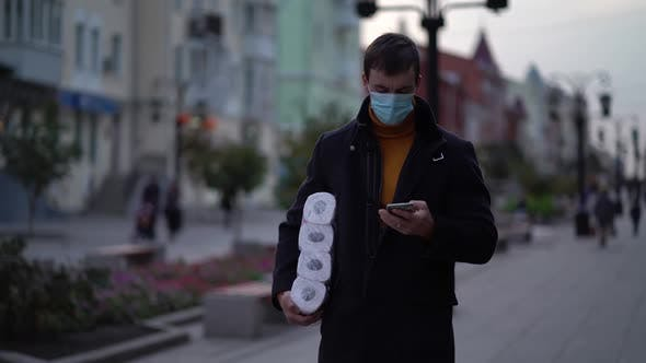 Thumbnail for Men Walking in Medical Mask with Toilet Paper and Smartphone During the Second Wave Quarantine