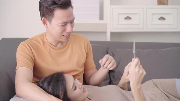 Asiatisches Paar mit Tablet für Online-Shopping im Internet im Wohnzimmer zu Hause, süß genießen Liebe.