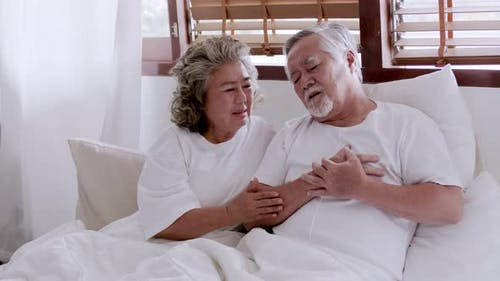 Asian elderly couple in bed, man's heart aches due to heart disease.