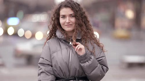 Pretty Young Female City Dweller Is Walking Alone on Street at Cold Day Medium Portrait of Charming