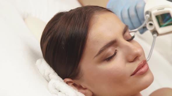 Lasertherapie auf der weiblichen Stirn im Kosmetologiezentrum