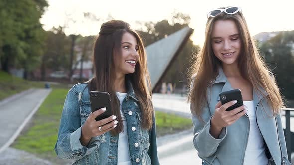 Thumbnail for two young attractive female friends with long hair using smartphone while walking